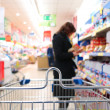 Woman at the supermarket with trolley — Stock Photo