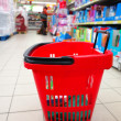Shopping basket with grocery at supermarket — Stockfoto