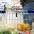 Shopping cart with grocery at supermarket — Lizenzfreies Foto