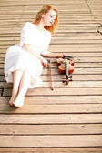 The blonde girl with a violin outdoor — Stock Photo