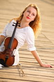 The blonde girl with a violin outdoor — ストック写真