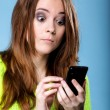 woman texting while looking surprised on phone — Stock Photo