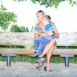 Happy family mother and son on bench in park — Stock Photo