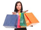 Retrato de mujer joven llevando bolsas contra blancos bac — Foto de Stock