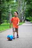 Boy kicks the ball in park outdoors — Stock fotografie