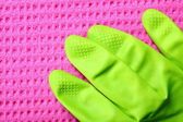 Pink sponge and green rubber glove — Stock Photo