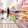 Stock Photo: Womat supermarket with trolley