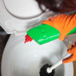 Stock Photo: Gloved hand cleaning toilet bowl using brush