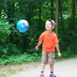 Boy playing with ball in park outdoors — Стоковая фотография