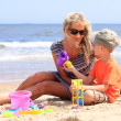 Son and mother playing toys on beach — Stock Photo