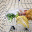 Shopping cart with grocery at supermarket — Foto Stock