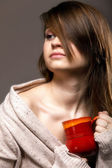 Pretty woman daydreaming while holding a tee cup — Stock fotografie