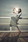 Girl on pier with kerosene lamp — Stock Photo