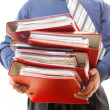 Male office worker carrying a stack of files — Stock Photo