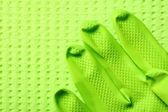 Green sponge and green rubber glove — Stock Photo