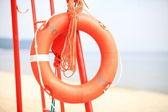 Lifeguard beach rescue equipment orange lifebuoy — Stock Photo