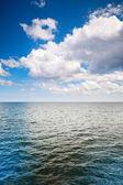 Deniz yüzeyinin üzerinde bulutlu mavi gökyüzü — Stok fotoğraf