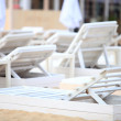 White pool chairs on sand beach — Stockfoto