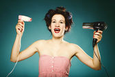 Funny girl in curlers with hairdryer styling hair — Stock Photo
