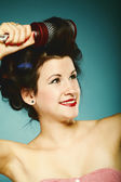 Girl in curlers with hairbrush styling hair — Stock Photo