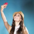 Girl with mobile phone taking photo of herself — Stock Photo #28879659