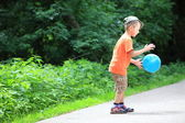 Boy playing with ball in park outdoors — Stok fotoğraf
