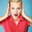Surprised young woman face over blue — Stock Photo #29141529