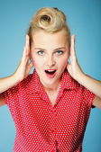Surprised young woman face over blue — Stock Photo