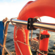 Rescue red lifebuoy on sail and blue sky sea — Stock Photo
