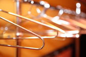 Empty metal clothes hangers in row indoor — Stock Photo