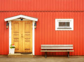 Wooden yellow door in orange colored building — Stock Photo