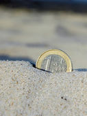 Euro coin in the sand — Stock Photo