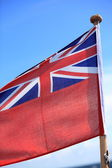 British maritime red ensign flag blue sky — Stock Photo