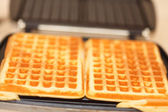 Waffle iron preparing waffles in kitchen — Stock Photo