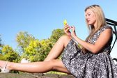 Young blonde girl in park texting on cell phone — Stock Photo