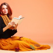 Autumn fashion girl with book orange eye-lashes — Stock Photo