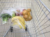 Shopping cart with grocery at supermarket — Stockfoto
