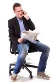 Man reads newspaper phoning - economy news — Stock Photo