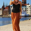 Stock Photo: Stylish traveler woman with camera old town Gdansk