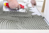 Construction worker is tiling at home, tile floor adhesive — Stock Photo