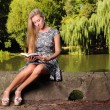 Blonde girl with book on green background of city park — Foto Stock