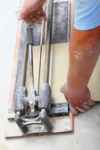 Construction worker is cutting tiles at home, renovation — Stock Photo