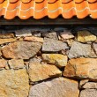 Stone wall with red clay roof — Stock Photo
