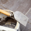 Foto Stock: Dirty trowel and bucket on building site. Renovation at home