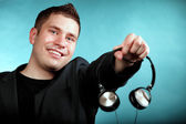 Music and technology, smiling man offering headphones — Stock Photo