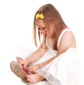 Child little girl tries to put on her shoes isolated — Stock Photo