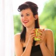 Beautiful Girl Drinking Tea or Coffee Indoor. Green Blurred Background — Stock Photo #32159743