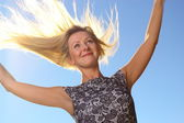 Young woman wind in hair outdoor outstretched arms — Stock Photo