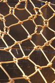 Knot rope netting orange safety net on ship metal background — Stock Photo