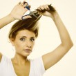 Unhappy woman cutting her hair with scissors — Stock Photo